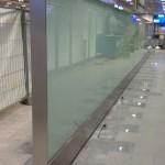 Flughafen Frankfurt, Ankunftsbereich, Sichtschutz aus Glas mit matter Folie, eingespannt in einer Stahl-Unterkonstruktion mit umlaufendem Edelstahlrahmen und Edelstahl-Blendleisten im Fußpunkt