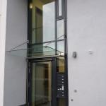 Betreutes Wohnheim Roth, Eingangsfassade mitm Ganzglas-Vordach und Edelstahlabhängern, sowie integrierte Briefkastenanlage